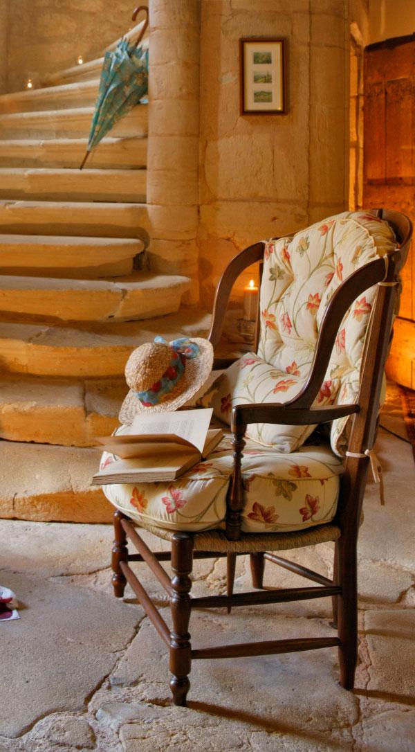 Salon donnant sur un fauteuil d'époque et un long escalier